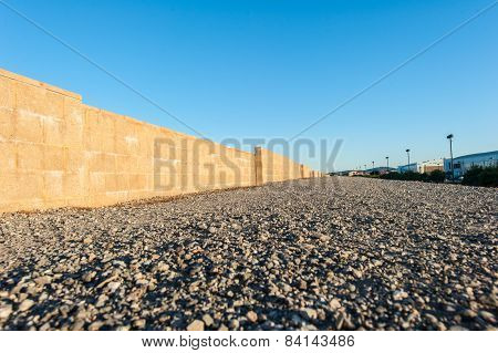 Gravel Covered Walking Path With Cinder Block Wall