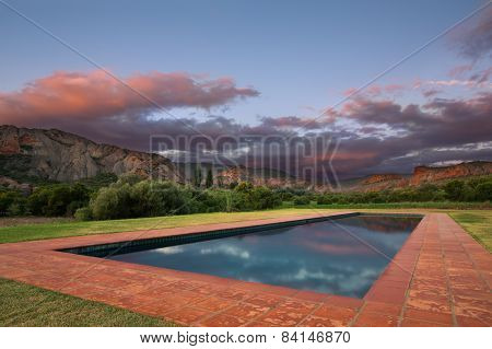 Cloudy Sunset With Red Rock Hills Reflect In Rectangular Pool