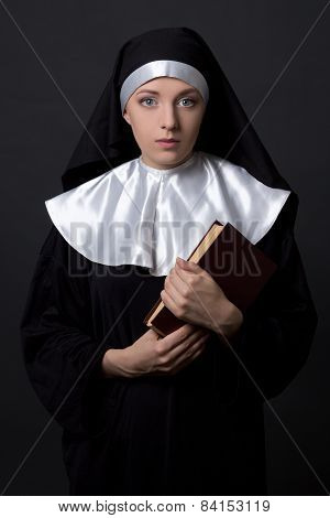 Woman In Nun Veil With Book Over Grey