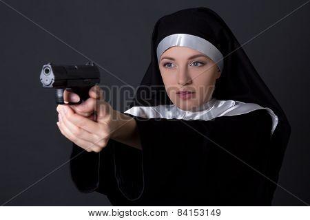 Young Woman Nun Shooting With Gun Over Grey