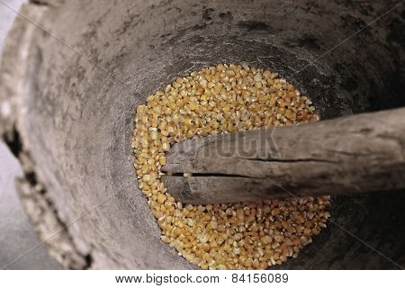 Corn being grinded with mortar and pestle made of wood to produce flour.