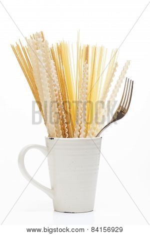 Mix Of Raw Pasta And Wholemeal Pasta In A Porcelain Cup And A Fork On A White Background