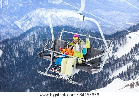 Happy boy with mother sit on skilift ropeway chair