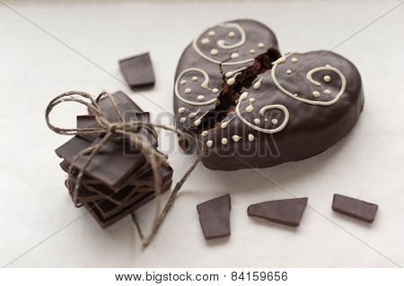 Broken ginger heart-shaped cookie with pile of dark chocolate
