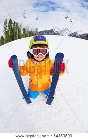 Boy wearing mask and helmet holds ski in winter