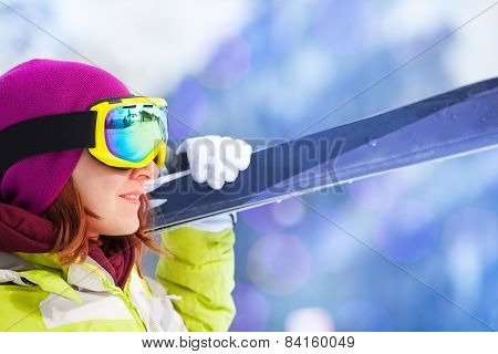 Close-up of happy woman in mask holding ski