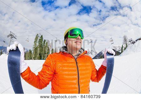 Smiling guy wearing mask holding ski in winter