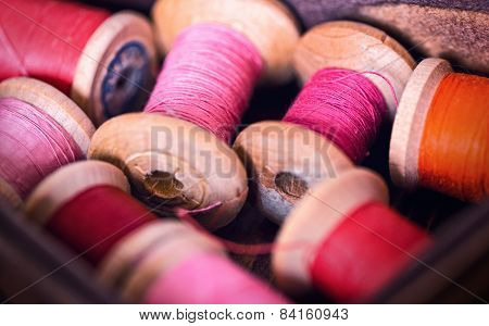 Collection Of Different Color Spools  Threads  Arranged In A Grunge Wooden Box