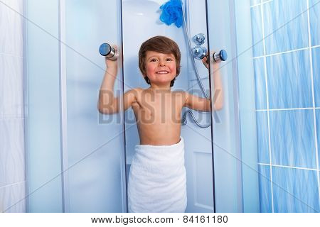 Happy little boy getting out of shower cabin
