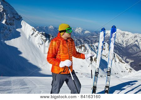 Man stands with ski in snow and mountains behind