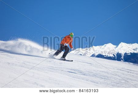 Sportsman in ski mask sliding fast while skiing