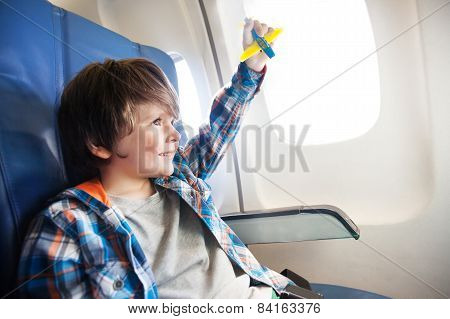 Little smiling boy with toy plane by the window
