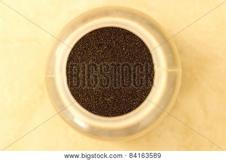 Himalayan tea dust stored in a container kept on a plain background