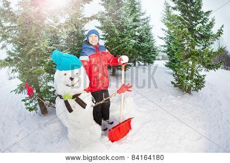 Arabian boy with shovel standing near snowman