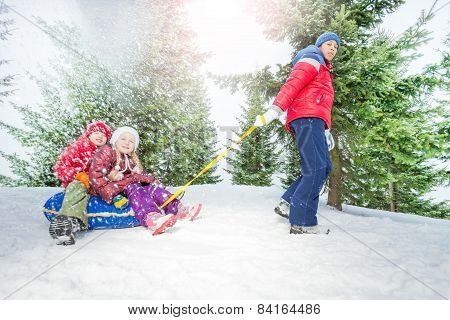 Children sit on snow tube and other boy pulls them
