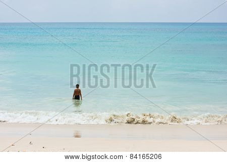A Young Boy Stands At The Ocean Shore