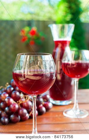 Two Glasses Of Delicious Homemade Red Wine With Grape.