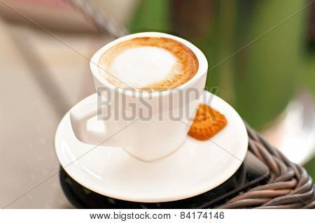 White Porcelain Cup Of Black Coffee With Milk On Rattan Table.