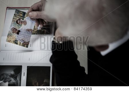 Windowed Man Watching Photo Album