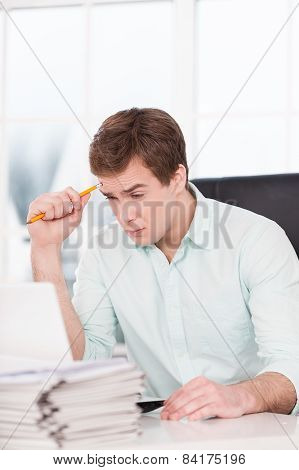 Young tired businessman looking at folders in office