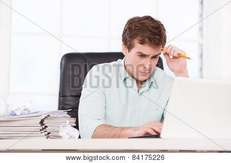 Young sad businessman looking at folders in office