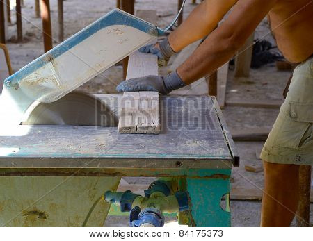 Carpenter cutting wooden planks with table saw.