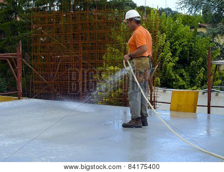 Construction worker watering fresh concrete slab