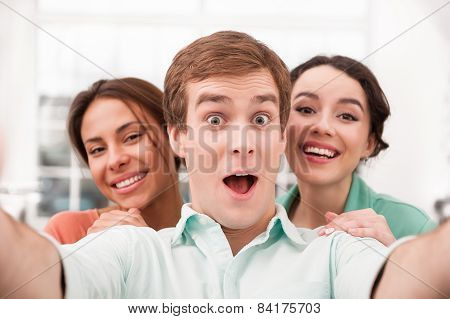Businessman and two businesswomen making photo on telephone