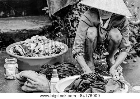 Old vietnamese woman is washing clothes