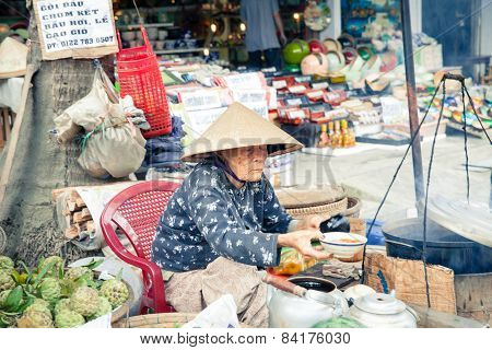 Women in conical hat selling food, Vietnam