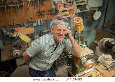 The Man Leaned His Elbow On The Wood Lathe In Workshop.