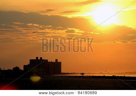 Sunrise and surfer in silhouette, Rockaway Beach New York