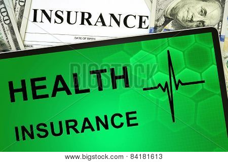 Tablet with Health insurance online and money.