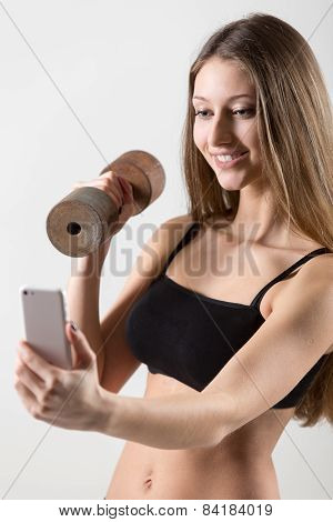 Smiling Sporty Girl Holding Dumbbell And Taking Selfie With Smartphone