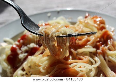 Spaghetti with ketchup and cheese on a plate.