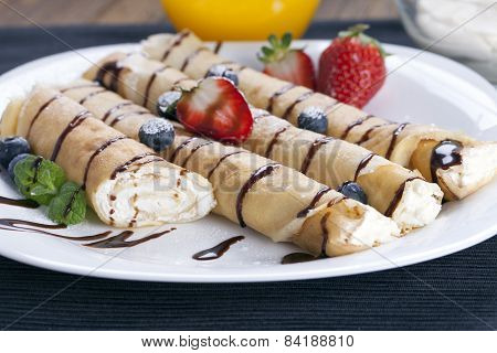 Delicious Sweet Rolled Pancakes On A Plate With Fresh Fruits