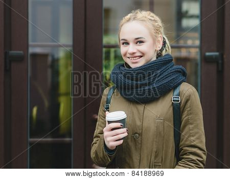 Young smiling cute hipster woman with dreadlocks bun holds a coffee cup