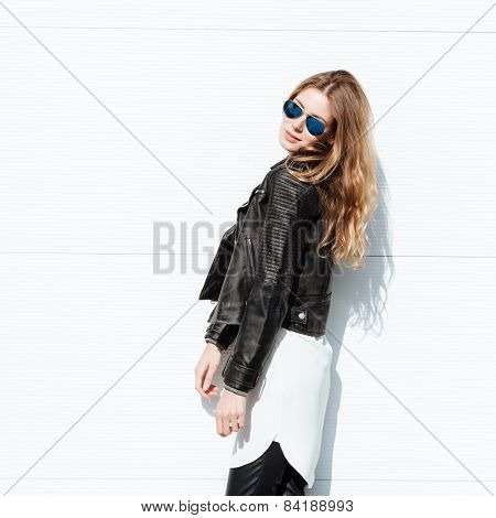 Young beautiful fashionable woman in leather jacket outdoors