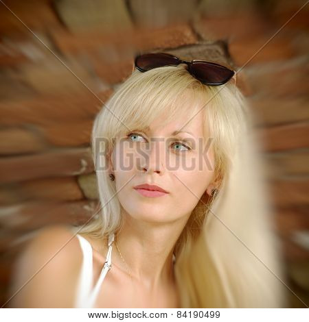 Beautiful Blonde On Brick Wall Background With Bokeh.