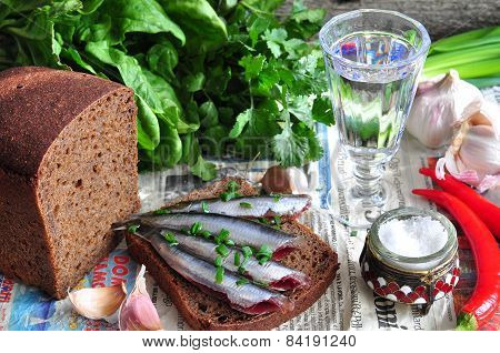 Russian traditions open sandwich with a sardines on rye bread with the wineglass of vodka