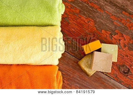 Handmade Soaps And Towels On Wooden Table