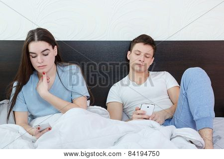Young attractive caucasian couple with smartphones