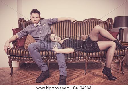 Elegant  Young Couple In Love Lying And Sitting On A Vintage Couch