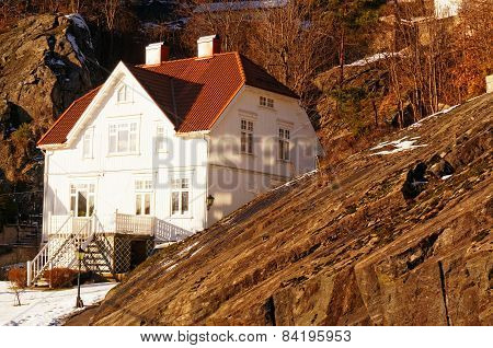 Norwegian White Wooden House Among Rocks