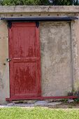 Weathered red door set in concrete wall poster