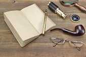stock photo of spyglass  - Open Vintage Notebook With Blank Pages Gold Fountain Pen Retro Magnifier Compass Glasses and Spyglass On Grunge Woodeen Table Background - JPG