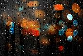 stock photo of rain  - Drops of rain on glass with colorful defocused lights - JPG