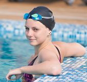 stock photo of goggles  - Portrait of a female swimmer wearing a swimming cap and goggles in blue water swimming pool - JPG