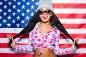 pic of black american  - Beautiful young black woman in funky clothes having fun while standing against American flag - JPG