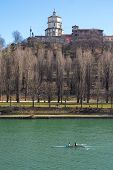 stock photo of turin  - Landscape of the church of Monte dei Cappuccini, on a small hill near the city of Turin, Piedmont North of Italy. In the foreground, rowers on the Po river. Vertical shot.